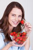 Fotografie Frau genießen eine Schale mit Erdbeeren