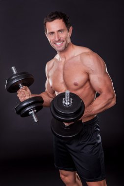 Young Attractive Man Pumping Weights