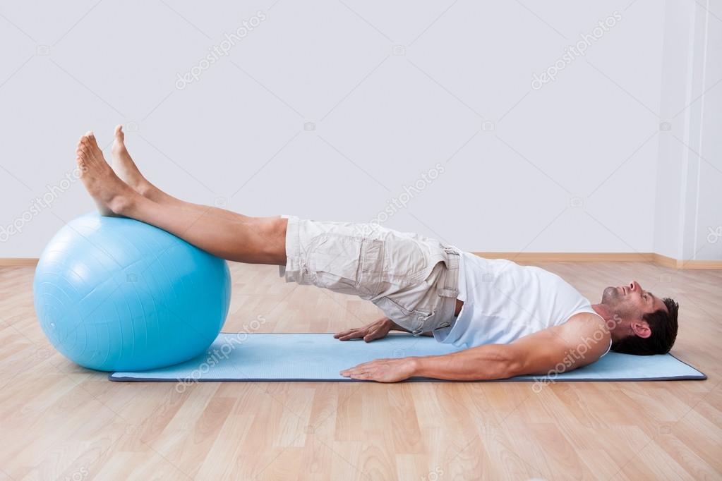 Young Man Exercising On A Pilates Ball