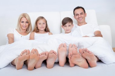 Happy Family In Bed Under Cover Showing Feet