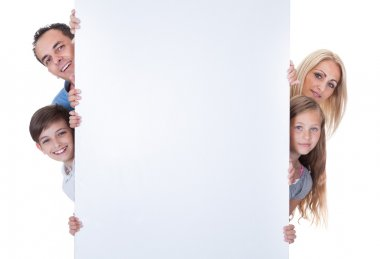 Portrait Of Family Peeping Behind Blank Board