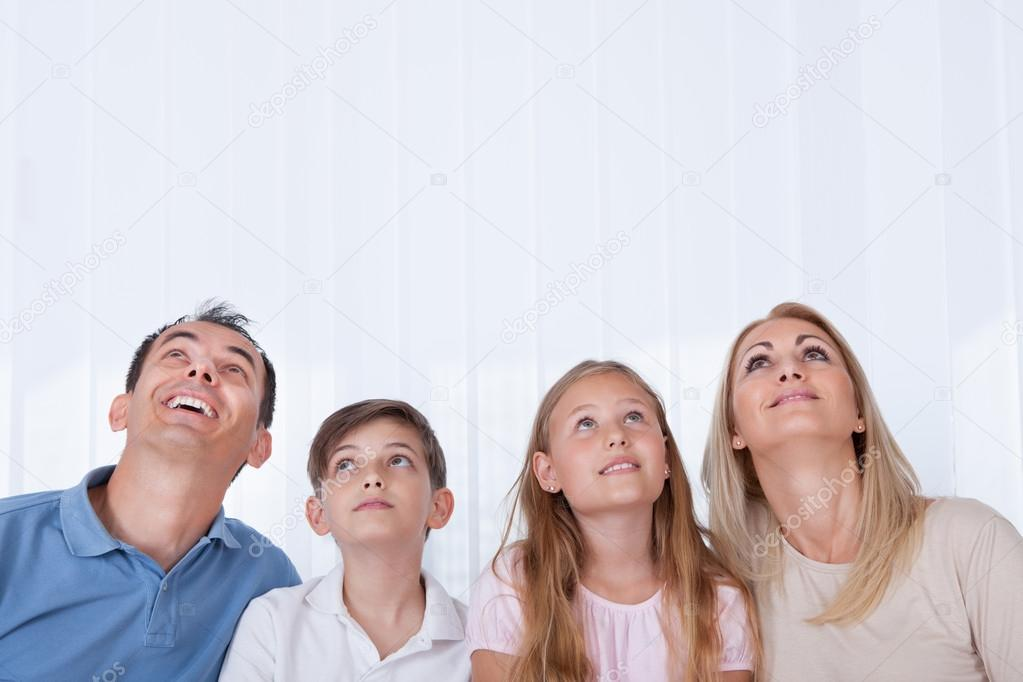 Portrait Of Family With Two Children Looking Up