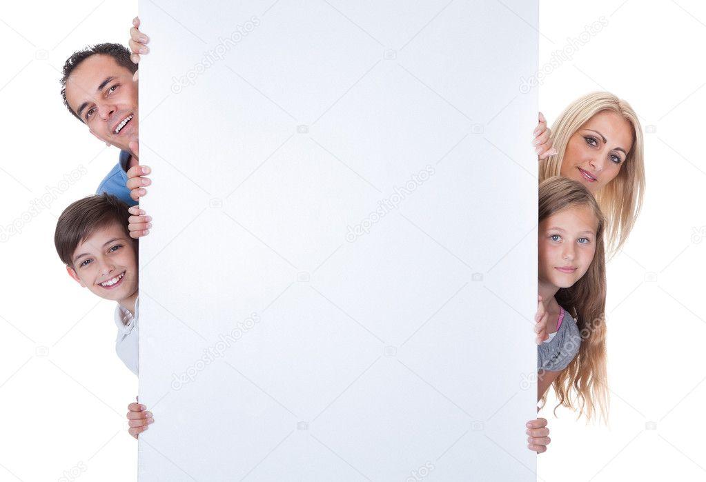Portrait Of Family Peeping Behind Blank Board