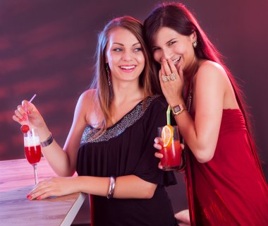 Two beautiful long haired female friends partying at a bar counter with cocktails in their hands under colorful lighting in a nightclub stock vector