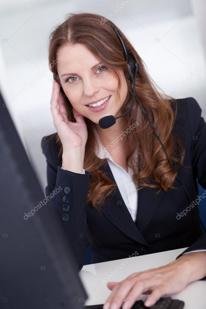 Smiling call center worker sitting typing