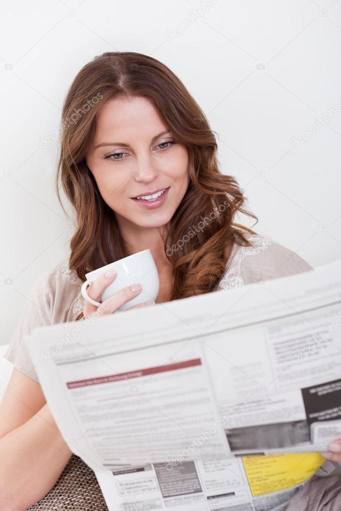 Woman reading the newspaper while drinking a refreshing cup of morning coffee