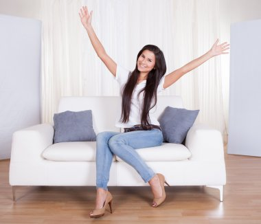 Happy woman sitting on a couch rejoicing