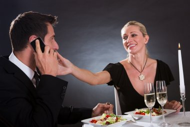 Man taking a mobile call during dinner