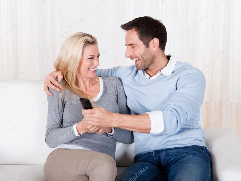 Young couple fighting for TV remote