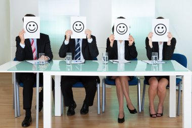 Row of business executives with smiley faces