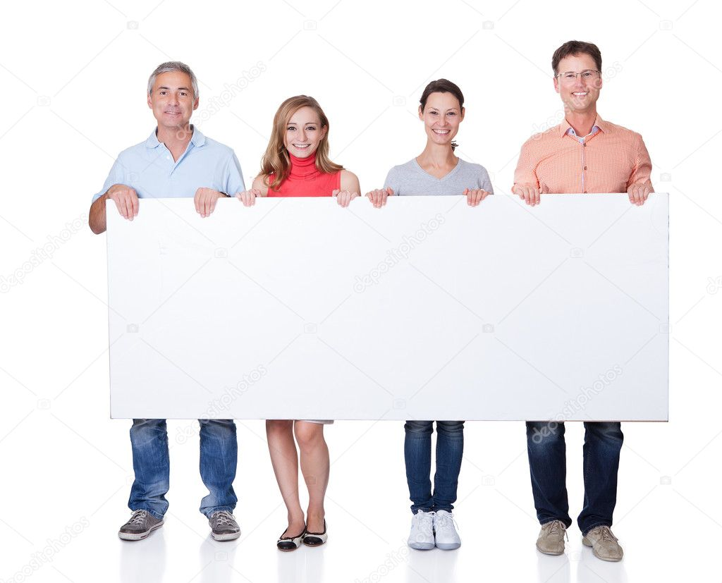 Two happy couples holding up a blank banner