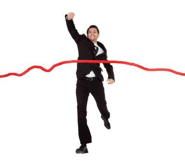 Businessman running through finishing line