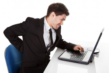 Businessman with lower back ache from sitting with a bad posture in his office chair working on his laptop massaging his back with his hand stock vector