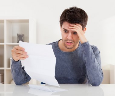 Horrified young man reading a document with an aghast expression and his hand to his forehead as he stares wide eyed at the page of paper stock vector