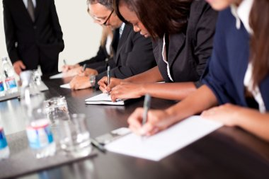 Group of business executives taking notes