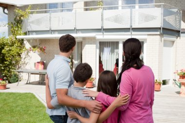 Young family standing in front of their dream home