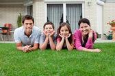 Fotografia Ritratto di una famiglia di quattro sdraiato nel cortile