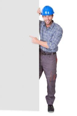 Portrait of happy worker presenting empty banner