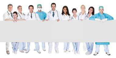 Group of doctors presenting empty banner. Isolated on white stock vector