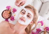 Kosmetička použitím obličejové masky na obličej ženy