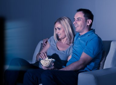 Couple Watching Television And Eating Popcorn At Home