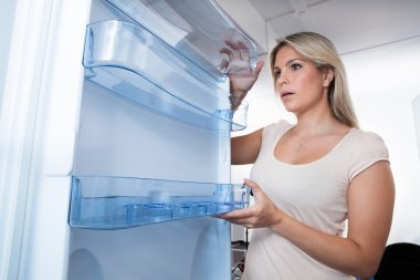 Young Woman Looking In Empty Fridge