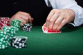 mano umana del giocatore di poker con carte e fiches