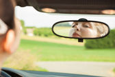 žena při pohledu na zrcadlo v autě