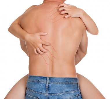 Rear view of muscular naked man and female hands