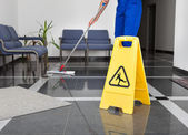 Photo Man With Mop And Wet Floor Sign