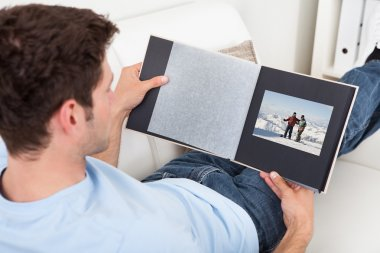 Man Looking At Photo Album