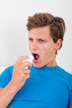 Young Man Using Asthma Inhaler For Preventing Attacks