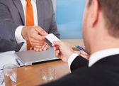 dva podnikatelé drží karty nad stůl