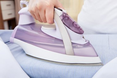 Person Ironing Clothes