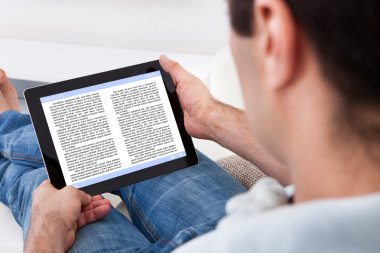 Man Holding Touch Screen Device Showing An E-book