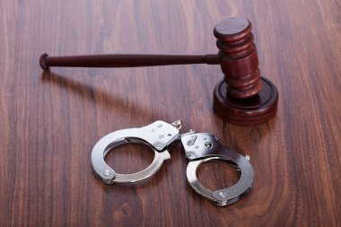 Gavel And Handcuffs On Wooden Table