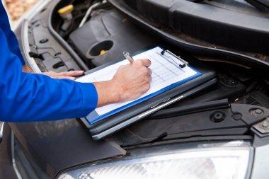 Mechanic Maintaining Car Records