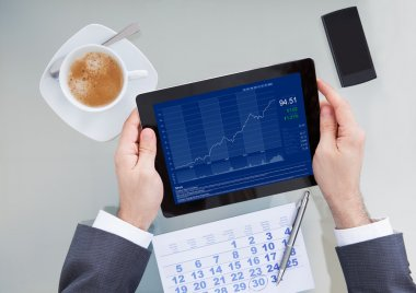 Businessperson Analyzing Graph On Digital Tablet In Office