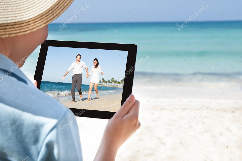 Woman Watching Video On Digital Tablet At Beach