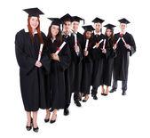 Postgraduální studenti stojící v řadě drží diplomy