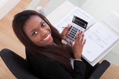 Confident Businesswoman Calculating Tax At Desk