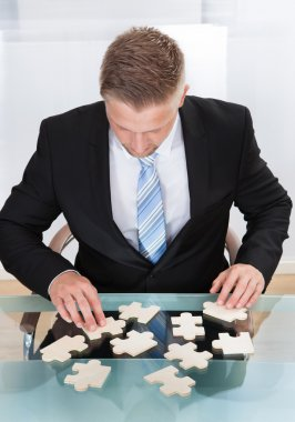 Businessman solving a jigsaw puzzle at his desk