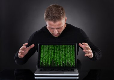Man or hacker stealing data from a laptop at night
