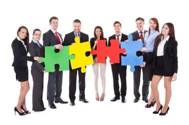 Group of businesspeople holding puzzle pieces