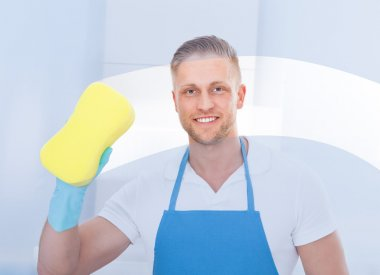 Male janitor using a sponge to clean a window