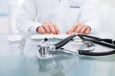 Conceptual medical and healthcare image with a close up of a stethoscope lying on a doctors desk with the hands of the doctor visible behind working on a computer stock vector
