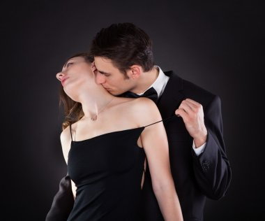 Man Kissing Woman On Neck While Removing Dress Strap