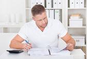 podnikatel pracuje u stolu v kanceláři