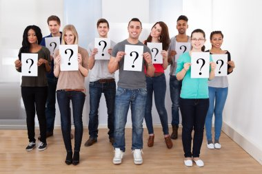 College Students Holding Question Mark Signs