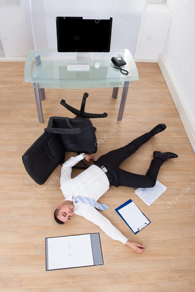 Businessman Fallen From Office Chair Stock Photo